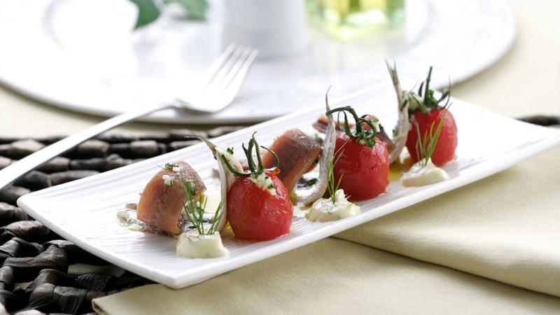 Matrimonio de anchoas y boquerones sobre tomates escaldados en soja
