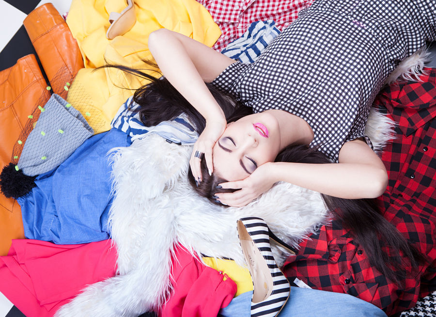 Nothing to wear concept, woman lying on a pile of clothes