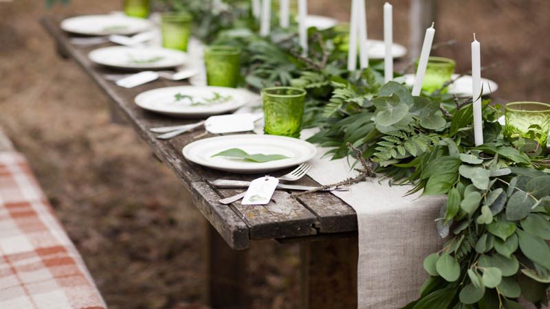 weddind table setting with white plates and green glasses decorated with white candles green leaves