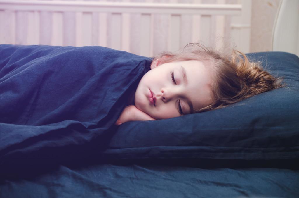 La privación del sueño puede resultar preocupante tanto adultos como para niños. Según estudios recientes, un tercio de los adultos no duermen lo suficiente. El sueño inadecuado representa un mayor riesgo de desarrollar enfermedades crónicas como: la obesidad, diabetes, hipertensión, enfermedades cardíacas, accidentes cerebrovasculares y la depresión. Con toda esta información, es importante saber cuánto debe dormir un niño según la edad. Los adultos de 18 a 60 años necesitan dormir al menos siete horas por noche para tener una salud óptima, y los adultos de hasta 64 años deben dormir de siete a nueve horas cada noche. Para los niños, no dormir lo suficiente puede ser particularmente problemático. Como sus cuerpos y mentes aún están en crecimiento, el sueño representa una parte crucial para un desarrollo saludable. Para un niño dormir lo necesario mejora la atención, el comportamiento, la salud emocional, mental y física, así como su capacidad de aprender y recordar. Por el contrario, cuando no duermen lo suficiente, sus cuerpos no son capaces de luchar contra las infecciones, cosa que es grave para los niños en edad escolar porque están continuamente expuestos a enfermedades contagiosas como los resfriados. La obesidad y los cambios de humor también están relacionados con la falta de sueño en los niños, y esos cambios de humor interfieren con la capacidad de concentración y el prestar atención. Conocer cuánto debe dormir un niño es especialmente importante para que los padres puedan tomar medidas y asegurarse de que sus niños estén durmiendo lo suficiente. Si tu hijo no está durmiendo lo suficiente porque pelea regularmente para irse a la cama, asegúrate de establecer buenas rutinas para dormir y habla con su médico si esas medidas aún no son suficientes. ¿Cuánto debe dormir un niño? A continuación te mostramos las siguientes recomendaciones de sueño para que tu niño tenga una salud óptima: Para bebés de 4-12 meses: de 12 a 16 horas, incluidas las siestas. Para niñ
